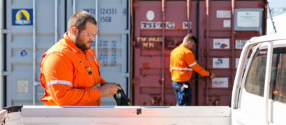 staff member putting gloves on with sea containers in the background